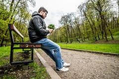 Jeune type attendant sa date posée sur le banc en parc Photographie stock libre de droits