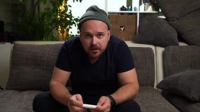 Jeune type attirant s'asseyant sur le divan et jouant la console Gagnez le jeu et sentez-vous heureux Homme utilisant le chapeau  banque de vidéos