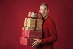 Jeune type avec des cadeaux à disposition sur le fond rouge image libre de droits