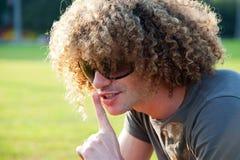 Jeune type avec le doigt sur ses languettes Photographie stock libre de droits