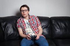 Jeune type avec les verres et la chemise rouge jouant des jeux vidéo sur la manette, se reposant sur un sofa en cuir noir photographie stock libre de droits