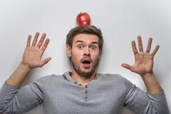 Jeune type beau équilibrant la pomme rouge sur sa tête Photos stock