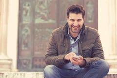 Jeune type beau détendant dans la vieille ville tenant le téléphone intelligent regardant l'appareil-photo image libre de droits