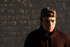 Jeune type beau dans une casquette de baseball sur le fond de mur de briques image stock