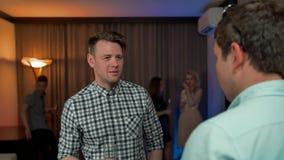Jeune type beau parlant avec son ami à la réunion intime banque de vidéos