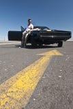 Jeune type beau se tenant dehors à côté de la voiture de muscle Images libres de droits