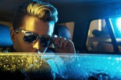 Jeune type beau utilisant les lunettes de soleil modernes Image stock