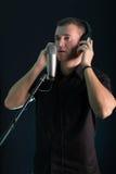 Jeune type chantant dans le microphone de studio Photos stock