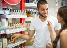 Jeune type choisissant le parfum dans la boutique Photos stock