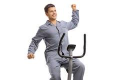 Jeune type dans les pajams s'étendant sur un vélo d'exercice image stock