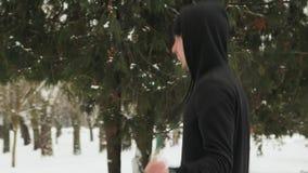 Jeune type dans un costume de sports dans noir, faisant des exercices, corde ? sauter dans un ext?rieur couvert de neige de parc  banque de vidéos
