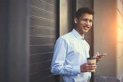 Jeune type de sourire de hippie dans la bonne humeur appréciant le café tandis que transmission de messages avec des amis Photos libres de droits