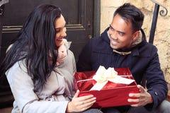 Jeune type donnant à son amie le cadeau de Noël Image libre de droits