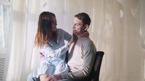 Jeune type et fille s'asseyant par la fenêtre dans une salle brillamment allumée, étreignant et embrassant banque de vidéos
