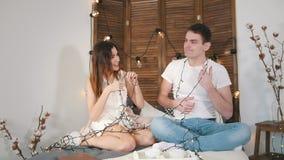 Jeune type et fille s'asseyant sur le divan, riant, flirtant et ayant l'amusement avec lumières banque de vidéos