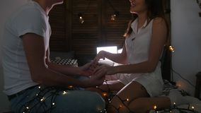 Jeune type et fille s'asseyant sur le lit, flirtant et ayant l'amusement avec lumières banque de vidéos