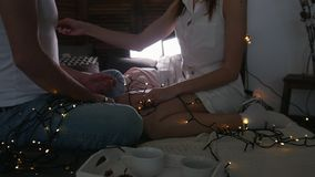 Jeune type et fille s'asseyant sur le lit, flirtant et ayant l'amusement avec lumières clips vidéos
