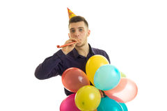 Jeune type gai soufflant dans le dudelku et tenant un ballon à air chaud Photos stock