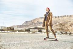 Jeune type heureux élégant dans un chapeau et des taqueurs de pantalons roulant vers le bas une route de montagne sur un longboar Photo stock