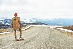 Jeune type heureux élégant dans un chapeau et des taqueurs de pantalons roulant vers le bas une route de montagne sur un longboar Images stock