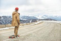 Jeune type heureux élégant dans un chapeau et des taqueurs de pantalons roulant vers le bas une route de montagne sur un longboar Photos stock