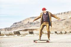 Jeune type heureux élégant dans un chapeau et des taqueurs de pantalons roulant vers le bas une route de montagne sur un longboar Photo libre de droits