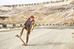 Jeune type heureux élégant dans un chapeau et des taqueurs de pantalons roulant vers le bas une route de montagne sur un longboar Image stock
