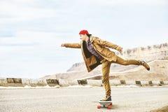 Jeune type heureux élégant dans un chapeau et des taqueurs de pantalons roulant vers le bas une route de montagne sur un longboar Photographie stock libre de droits
