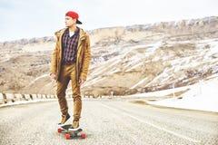 Jeune type heureux élégant dans un chapeau et des taqueurs de pantalons roulant vers le bas une route de montagne sur un longboar Photographie stock