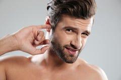 Jeune type impoli sélectionnant son oreille et regardant l'appareil-photo Photo stock
