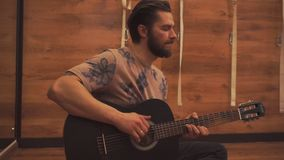 Jeune type jouant la guitare closeup banque de vidéos