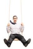 Jeune type joyeux balançant rapidement sur une oscillation Photo libre de droits