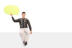 Jeune type jugeant une bulle de la parole posée sur le panneau Photo stock