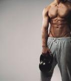 Jeune type musculaire avec la cloche de bouilloire Photos libres de droits