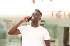 Jeune type noir heureux se tenant dehors et faisant un appel téléphonique images libres de droits