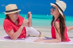 Jeune type photographiant sa belle amie sur la plage blanche Image libre de droits