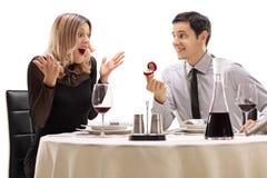 Jeune type proposant à son amie à une table de restaurant Photographie stock libre de droits