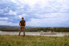 Jeune type regardant au-dessus de la rivière sur la ville Photo libre de droits