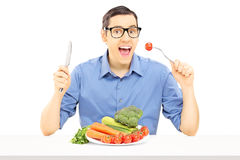 Jeune type s'asseyant à la table mangeant des légumes photos stock