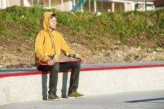 Jeune type s'asseyant en parc de patin examinant la distance et tenant une planche à roulettes Photo libre de droits