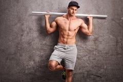 Jeune type sans chemise tenant un tuyau en métal photo libre de droits