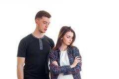 Jeune type se tenant à côté de la fille faite du tort qui regarde vers le bas photos libres de droits
