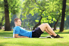 Jeune type se trouvant sur un tapis en parc Image stock
