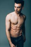 Jeune type sexy musculaire posant dans le studio dans des jeans Images stock
