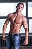 Jeune type sexy musculaire posant en jeans et torse nu Images libres de droits