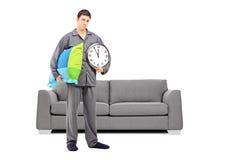 Jeune type somnolent tenant une horloge murale et un oreiller, avec moderne ainsi Photographie stock