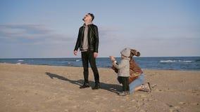 Jeune une famille moderne et élégante avec leur petit fils se tiennent ensemble sur le littoral près de la mer Jeu avec a banque de vidéos