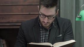 Jeune universitaire en verres lisant attentivement un livre banque de vidéos