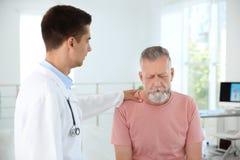 Jeune urologue soulageant le patient bouleversé Photo libre de droits