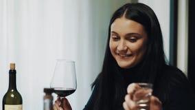 Jeune verre de vin de parler et de boissons de femme de brune à la table de dîner banque de vidéos